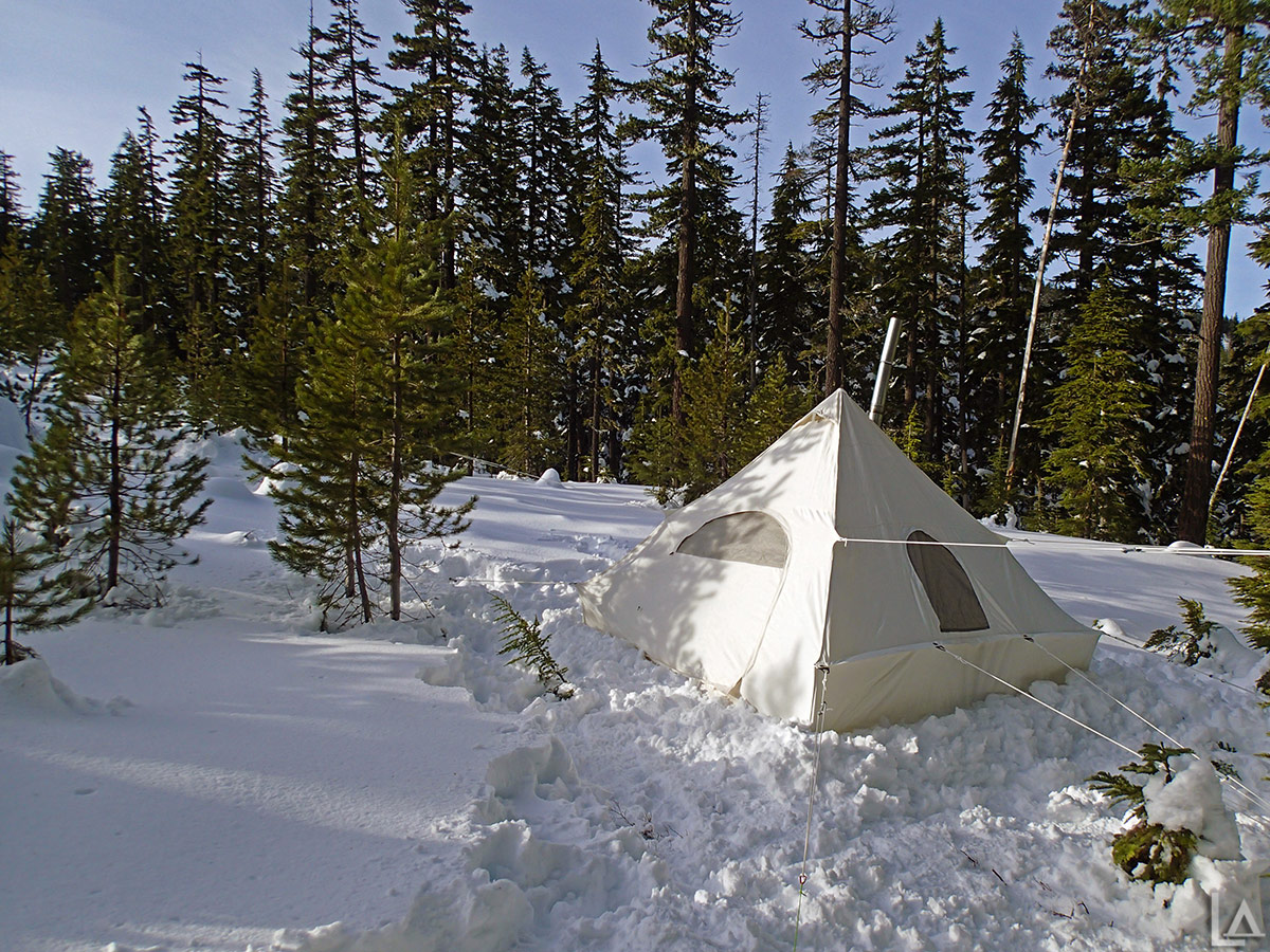 Canvas pyramid tent setup in the snow