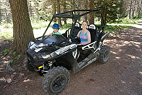 Katie and our Mini Adventurer ready for a ride in a Polaris RZR 900