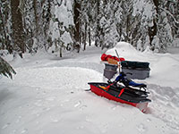 Snow camping gear hauled in by snowmobile