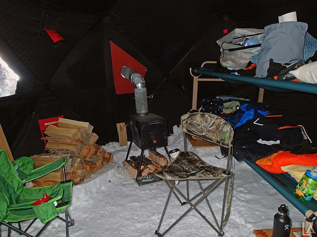The inside of our Eskimo tent with wood stove and bunk bed cots