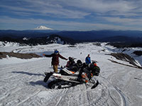 Snowmobiling up Mt St. Helens looking down and over at Mt Adams