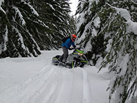 Kevin turning around his Arctic Cat snowmobile on a narrow trail